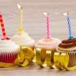 Four birthday cupcakes on table — Stock Photo