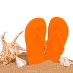 Orange sandals and seashells in sand — Stock Photo
