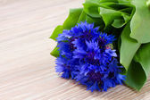 Blue corn flowers on wooden table — Stock Photo