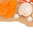 Orange sandals and seashells on sand — Stock Photo