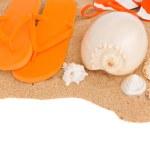 Orange sandals and seashells on sand — Stock Photo
