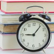 Stock Photo: Alarm clock on books background
