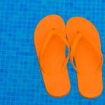 Flip flops in pool water — Stock Photo #27422549