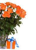 Rosas naranjas frescas en florero con regalo — Foto de Stock