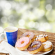 Coffee mug and plate of donuts — Stock Photo