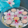 Spa with floating orchideas and candles — Stock Photo