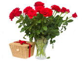 Bunch of red roses in vase with gift basket — Stock Photo