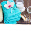 Spa settings with blue towels and aroma candle — Stockfoto