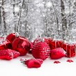 Red christmas balls in snowed forest — Stock Photo