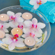 Burning candles and orchid flowers in water — Stock Photo