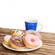 Plate of donuts and blue coffee mug — Stock Photo
