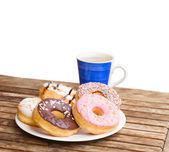 Plate of donuts and blue coffee mug — Stock fotografie