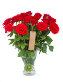 Bouquet of scarlet roses in vase with tag — Stock Photo