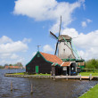 Dutch windmill over  river waters — Stock Photo