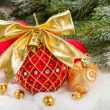 Red christmas ball with golden bow in snow — Stock Photo