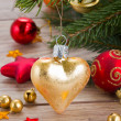 Golden heart on fir tree — Stock Photo