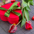 Red gift box and  tulips — Stock Photo