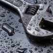 Adjustable spanner in water drops close up — Stock Photo
