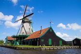 Old dutch windmill over river waters — Stock Photo