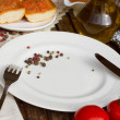 Stock Photo: Empty plate and bread with tomatoes and olive oil