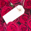 Bouquet of dark red roses with tag — Stock Photo