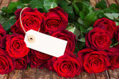 Dark red roses with empty tag — Stock Photo