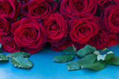 Fresh red roses on table — Stockfoto