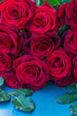 Fresh red roses on blue table — Stock Photo