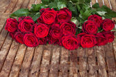 Dark red roses on table — Stock fotografie