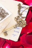 Antique Key with old papers and rose petals — Stock Photo