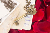 Key with old papers and rose petals — Stock Photo