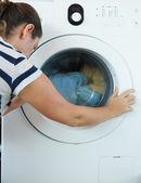 Woman loading laundry — Stock Photo
