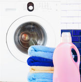 Towels with detergent and washing machine — Stock Photo