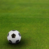Soccer ball on green football field — Stock Photo