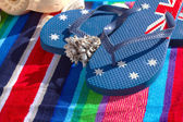 Blue flip flops on beach towel — Stock Photo