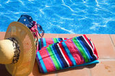 Towel and bathing accessories near pool — Stock Photo