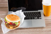 Eating at work place fast food near laptop — Stock Photo