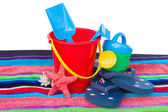 Beach toys with flip flops and starfish on towel — Stock Photo