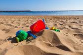 Beach toys in sand on sea shore — Stock Photo