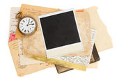 Pile of old photos with antique clock — Stock Photo