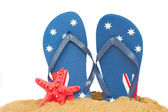Blue  sandals and starfish in sand — Stock Photo