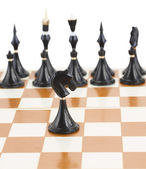 Black knight in front of black chess — Stok fotoğraf