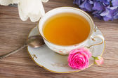 Antique cup of tea with flowers — Stock Photo
