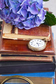 Pile of old books with flowers and clock — Stock Photo