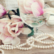 Magnolia flowers with pearls on wooden table — Stock Photo #45231537