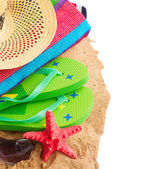 Sunbathing accessories and straw hat on sand — Stock Photo