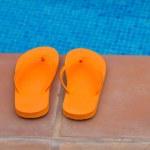 Orange flip flops on pool edge — Stock Photo