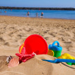 Bucket with plastic beach toys in sand on sea shore — Stock Photo #46513427