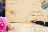 Antique empty postcard with flowers and quill pen — Stock Photo
