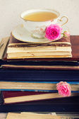 Pile of old books and mail with cup of tea — Stock Photo